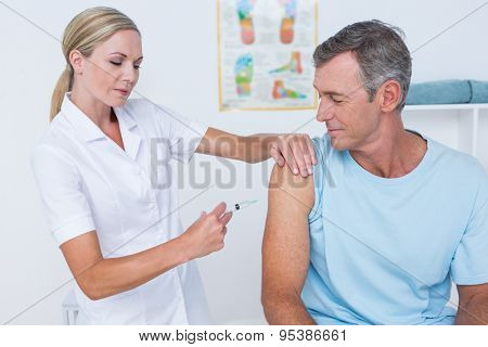 Doctor doing an injection to her patient in medical office