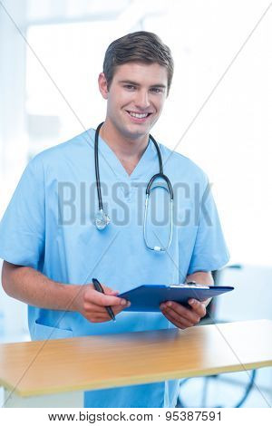 Smiling doctor looking at camera and holding clipboard in medical office