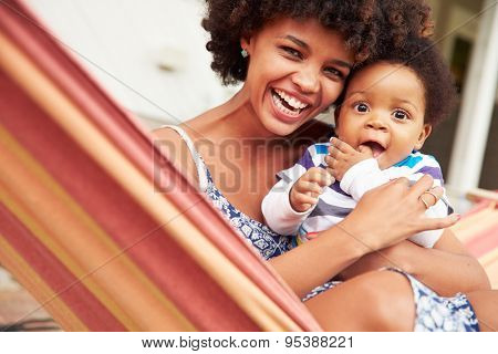 Mother bonding with young son sitting in a hammock, portrait