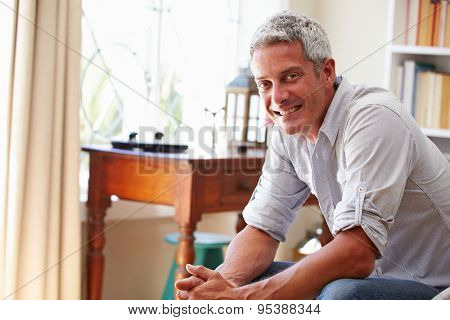 Portrait of�¿a smiling grey haired man sitting in a room