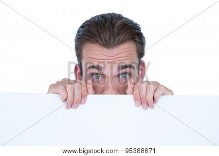 Man hiding by blank paper on white background