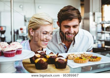 Cute couple on a date looking at cakes at the bakery