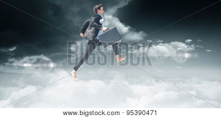 Leaping businessman against bright blue sky with clouds