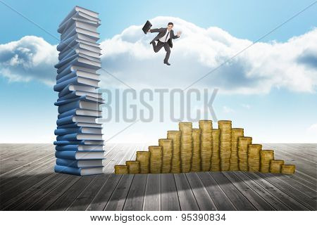 Smiling businessman in a hurry against stack of books against sky