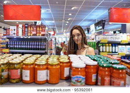 young woman shopping for fruits and vegetables in produce department of a grocery store supermarket