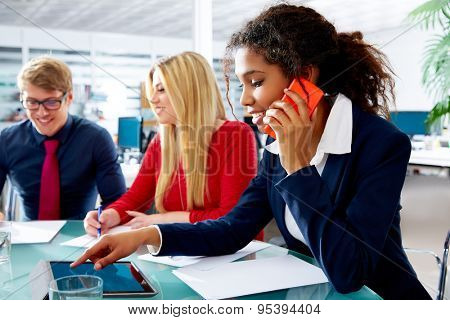 African businesswoman talking phone and touch pad in teamwork meeting at office