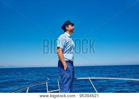 Beard sailor man sailing sea ocean in a boat with captain cap looking horizon