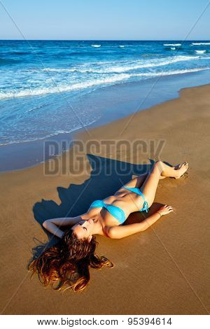 Beatiful brunette bikini girl lying on beach sand in summer vacation