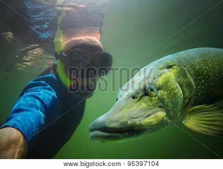 Underwater selfie with friend. Scuba diver and pike in deep lake.
