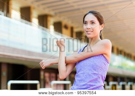 Woman stretching hand at sport stadium