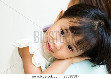 Little girl lay on mother shoulder