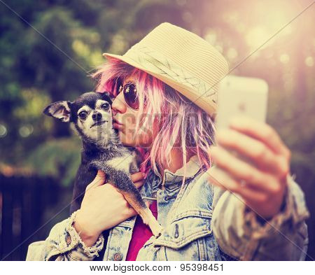 Young woman taking a selfie with a cute chihuahua dog toned with a retro vintage instagram filter effect app or action