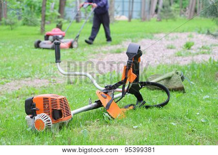 lawn mower and edge trimmer in the garden