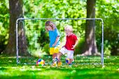 Постер, плакат: Children Playing Football Outdoors