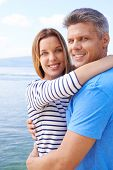 picture of amor  - Amorous couple in embrace looking at camera by the sea - JPG