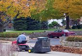 foto of leaf-blower  - man clearing leaves in street and parking lot - JPG