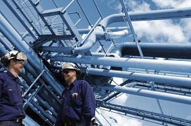 pic of pipeline  - oil and gas workers with refinery pipelines in background - JPG