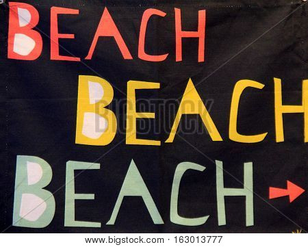 Black background with the word 'beach' printed in colors