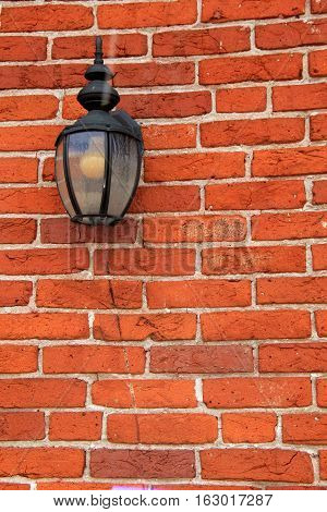 Colorful red brick background with old, weathered wrought iron  lantern attached to face of it.