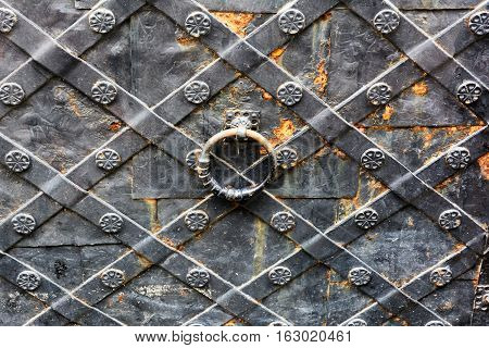 Old wrought-iron gates. Metal door with a pattern.