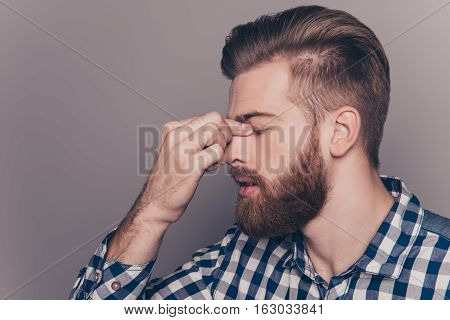 Side-view Portrait Of Tired Sick Handsome Young Man With Strong Migraine Grimace Isolated Gray Wall