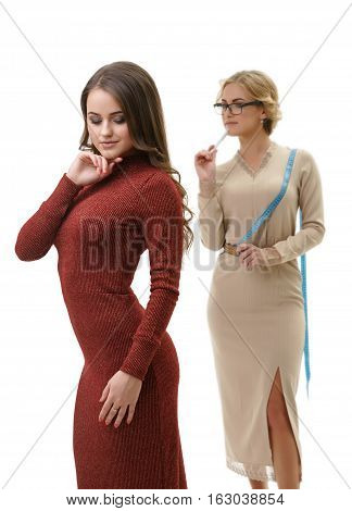 Young sexy dressmaker in slinky beige dress takes measurements of her cute slim long haired client in sexual knitted winy gown studio shot