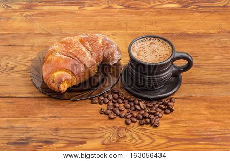 Freshly brewed coffee latte in a black ceramic cup roasted coffee beans and croissant on a glass saucer on an old wooden surface