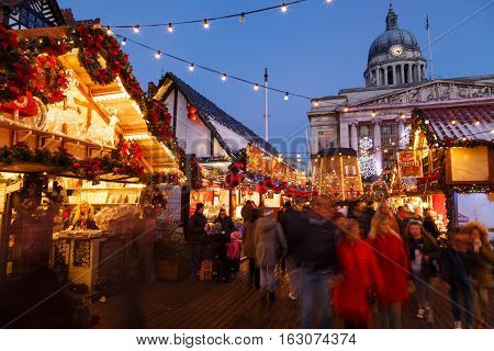 NOTTINGHAM ENGLAND - DECEMBER 22: Families enjoying Nottingham Christmas Market in the evening. In Nottingham England. On 22nd December 2016.