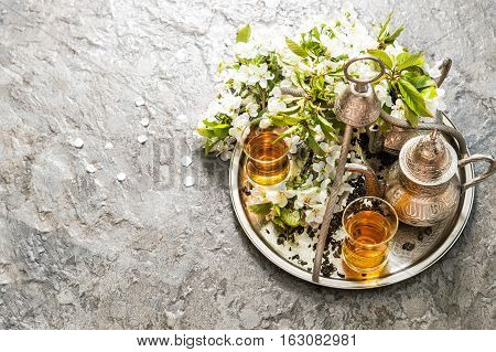 Tea glasses and pot. Oriental silver tableware. Spring flowers decoration. Selective focus