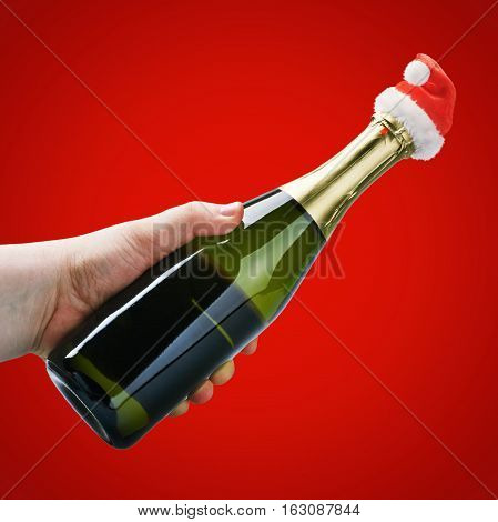 hand holding a champagne bottle in a Christmas decoration santa clothes on a bordo background