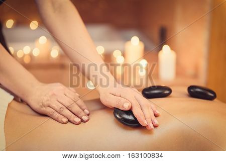 Close up of arms of professional beautician is undergoing massage for young woman. She is pampering female back by black stones