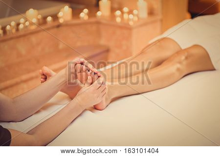 Close-up of female feet getting relaxing massage by masseuse at spa
