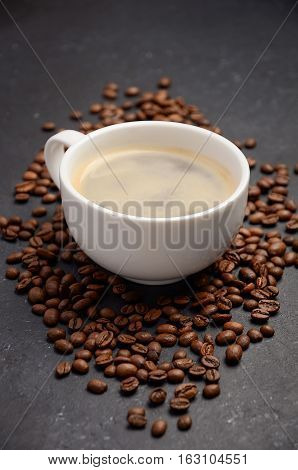 Cup of fresh coffee with coffee beans on black background, selective focus, vertical.