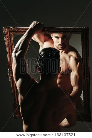 Handsome man or muscular bodybuilder macho with sexy muscle torso body with six packs and abs triceps biceps in white sexi underpants looks at mirror on grey background