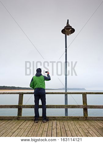 Alone Tourist Guide At Sea Pier Handrail, Autumn Misty Morning.man Stay Bellow Old Lamp.