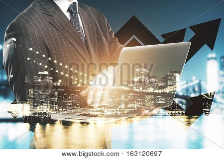Abstract image of young man using laptop on city background with business charts. Double exposure. Success concept