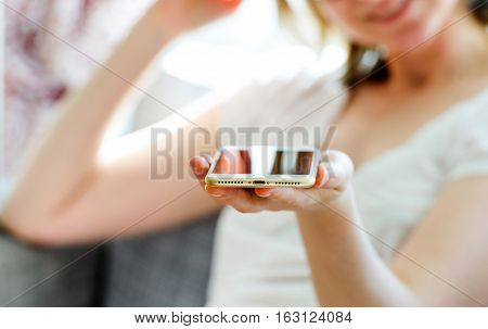 PARIS FRANCE - SEP 29 2016: Woman presenting the new iPhone 7 Plus with lightning and no mini jack 3.5 mm. New Apple iPhone tends to become one of the most popular smart phones in the world in 2016