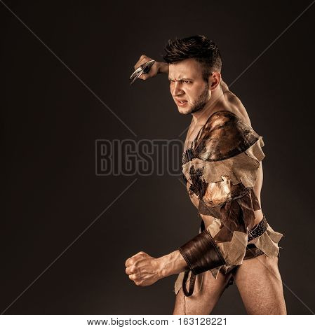 Portrait of handsome muscular gladiator with sword. Isolated. Studio shot. Black background