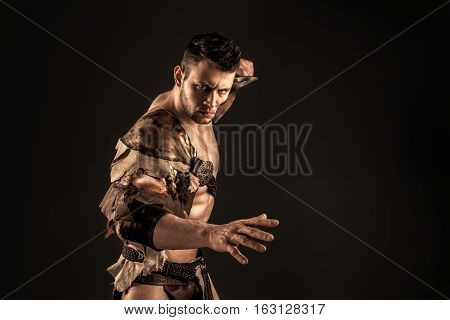 Portrait of handsome muscular gladiator with sword near face. Isolated. Studio shot. Black background