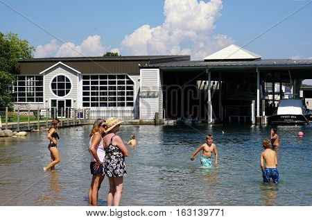 HARBOR SPRINGS, MICHIGAN / UNITED STATES - AUGUST 3, 2016: People enjoy swimming in the water at the Zorn Park Public Beach near downtown Harbor Springs.