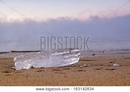Piece Of Ice On The Sand Beach. Close up View.