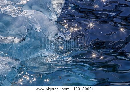 Pieces Of Iceberg Drifting At The Shore And Sun Beams Shining On The Water Surface, Greenland