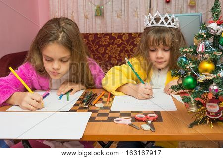 Two Girls Writing Christmas Greeting Letter Sitting At The Table At Home