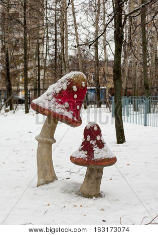 sculpture toadstools, with red hats in the winter snow park
