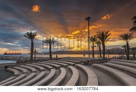 Colorful sunset at the Red Sea; view from stone amphitheater on central beach of Eilat - famous resort and recreational city in Israel