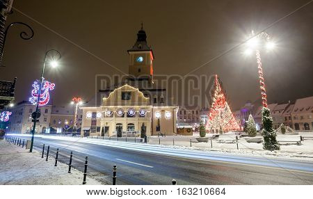 BRASOV ROMANIA - 15 DECEMBER 2016: Brasov Council House night view with Christmas Tree decorated and traditional winter market in the old town center Romania