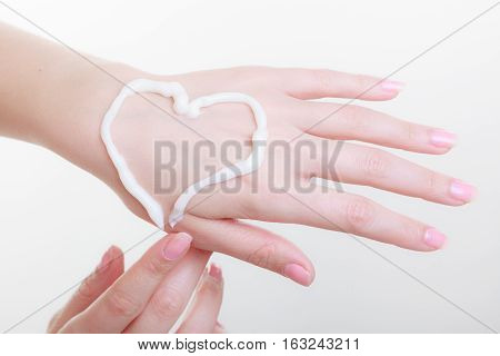 Beauty cosmetics concept. Cream on woman hand heart shape. Studio shot on white background