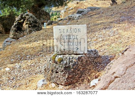 Pointer of ruins of stage theater in Delphi, Greece