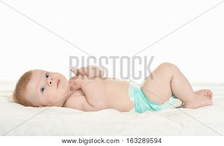 dorable baby boy in pampers on blanket on a white background