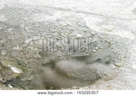Pieces of ice in water and reflection of clouds in lake in sunny day